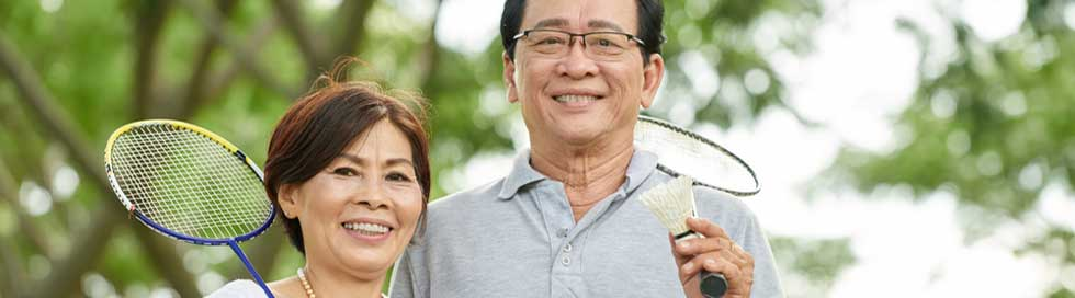 Man and woman hold badminton racquets
