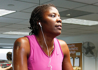 Healthy African American woman exercising at a gym.