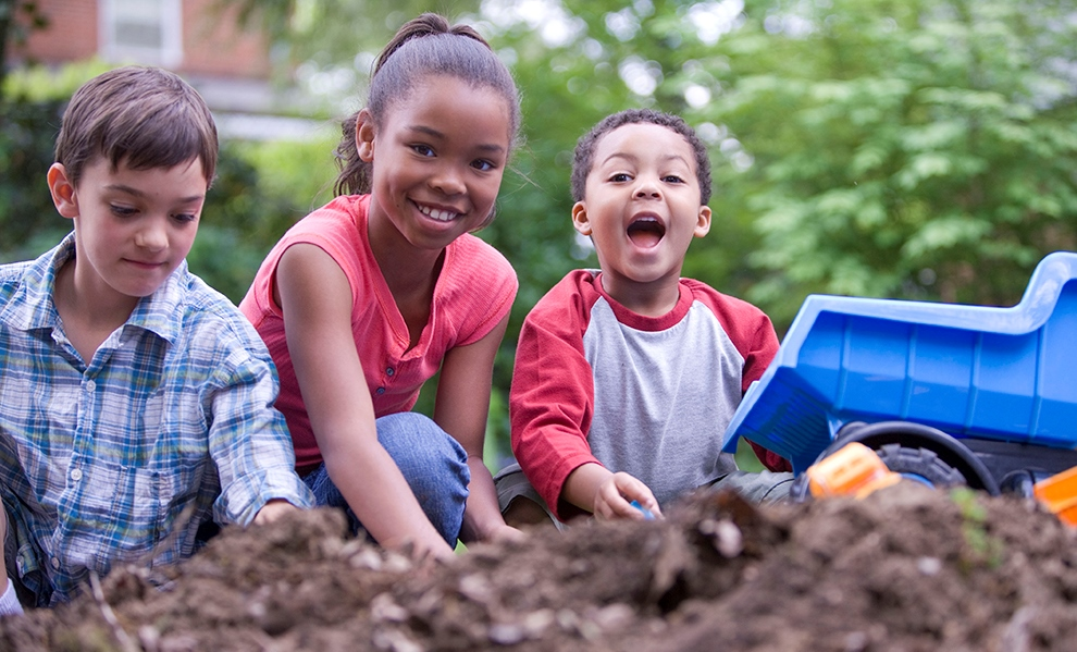 Photo of kids playing together in the dirt.