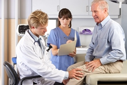 Photo of two medical professionals examining a man's knee.