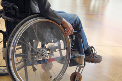 Photo showing a person's legs as he sits in a wheelchair.