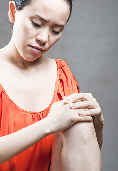 Photo of a woman in a orange shirt holding her knee.