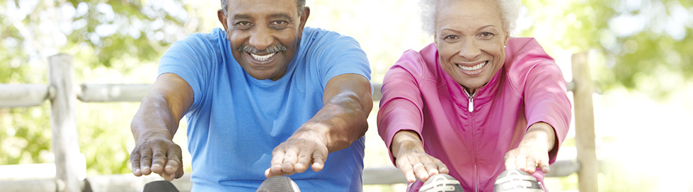 An older woman and man stretching for exercise.