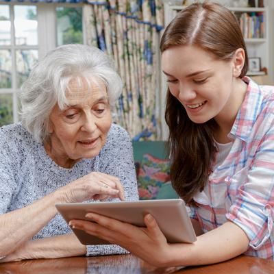 An elder and a young girl looking at a tablet