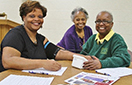 Community members Karen McDowell (left) and Janice Flemming (center) have their blood pressure checked by Chi Eta Phi nurse Gwendylon Johnson (right) at a recent Kidney Sundays event.