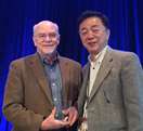 John O'Shea, M.D., (l) receives his award from ICIS President Tada Taniguchi, Ph.D.