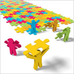 colored people placing color puzzle pieces down