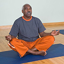 A man sitting with his eyes closed meditating.