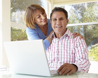 A elder couple look at a laptop