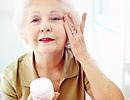 elderly woman rubbing lotion on her face