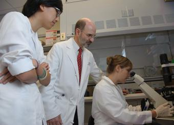 Robert Colbert M.D. Ph.D. Amy Petrik Ph.D. and Grace Kwon Ph.D. Examine Skin Fibroblasts under a Microscope.