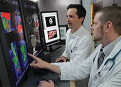 Dr. Peter Grayson (left), principal investigator of NIH's Vasculitis Translational Research Program, reviews diagnostic images with Dr. Mark Ahlman at the NIH Clinical Center.