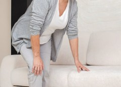 Photo of a woman having trouble getting up from a couch due to knee pain.