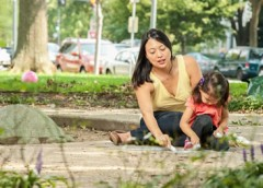 Photo of woman and child playing with sidewalk chalk.